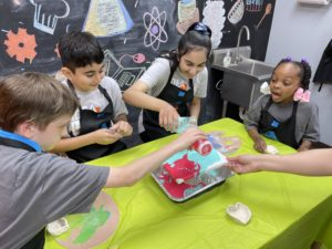 Four kids pouring paint on a canvas