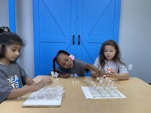 Three girls assembling structures with marshmallows and toothpicks
